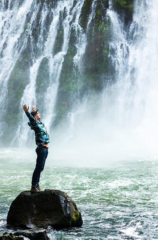 man rejoicing a waterfall QI